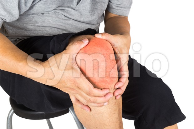 Matured man suffering from painful knee joint seated on stool Stock Photo