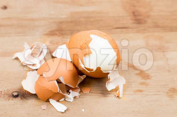 Hard boiled eggs with shell peeled on wooden table Stock Photo