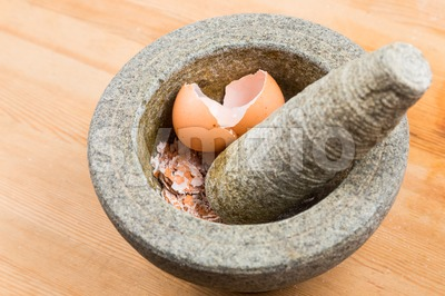 Kitchen mortar and pestle with crashed egg shell Stock Photo