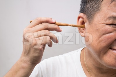 Man un-hygienically cleaning ear using wooden stick Stock Photo