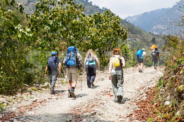 A group of people trekking on dirt road in Nepal Stock Photo