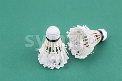 Two worned out used badminton shuttlecock  on green court mat Stock Photo