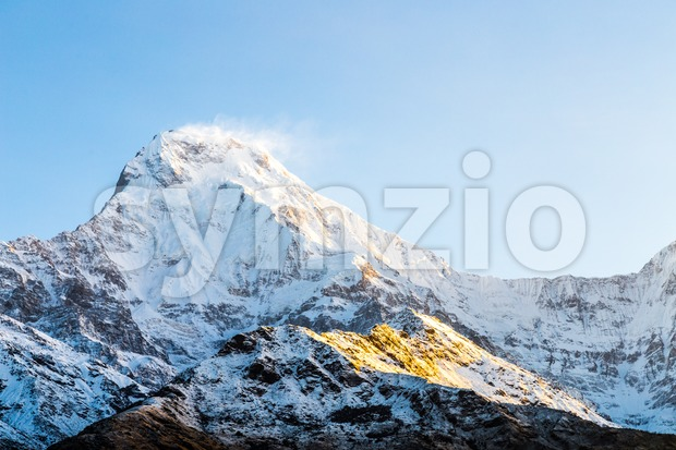 Sunrise rays on the snowcappped peak of Annapurna South Stock Photo