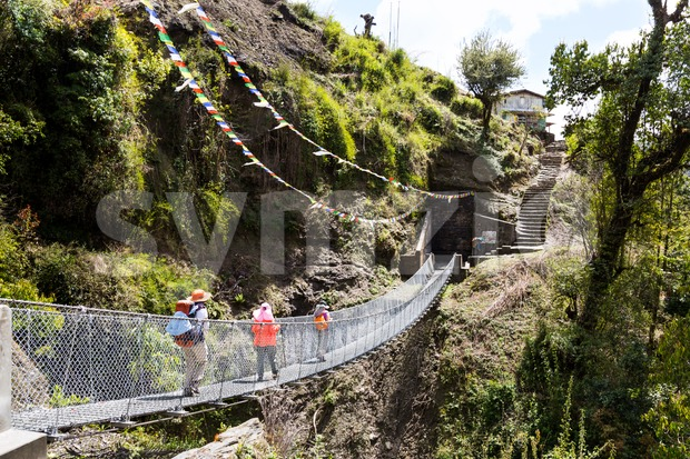 Three hikers walking through a suspension bridge in Nepal Stock Photo