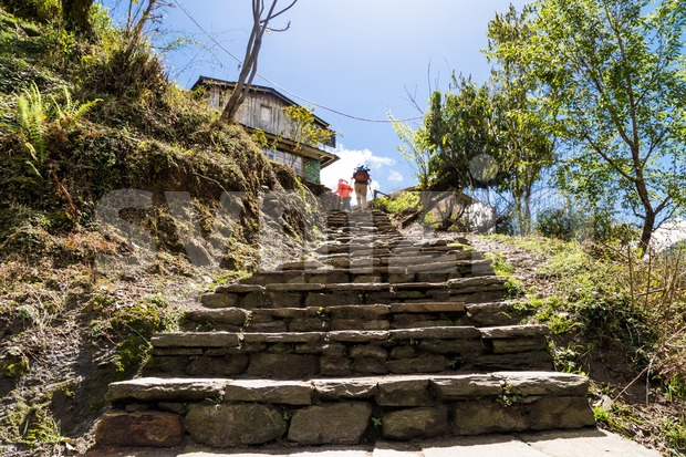 Hikers ascending a long and steep flight of steps in Nepal Stock Photo