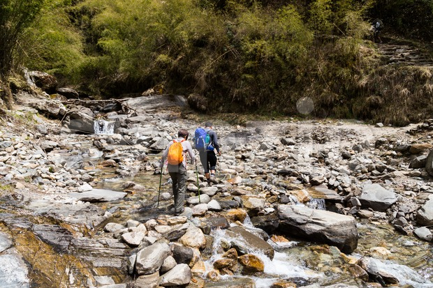 Two hikers crossing a scenic shallow rocky river en-route to Annapurna Base Camp, Nepal Stock Photo