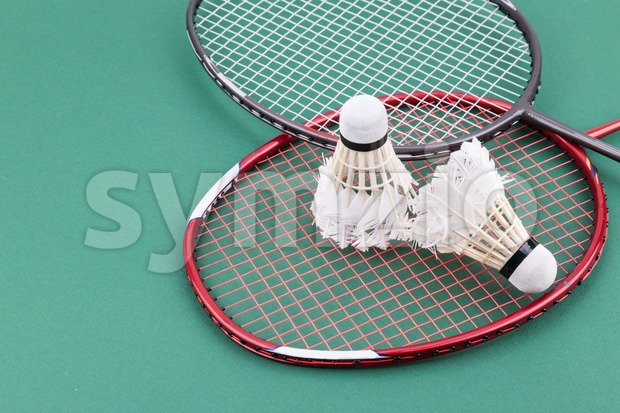 Two worned out badminton shuttlecock with racket on green court Stock Photo