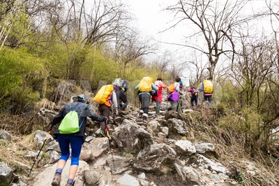 A group of people trekking an ascending rocky trail to the mountains of Annapurna, Nepal Stock Photo