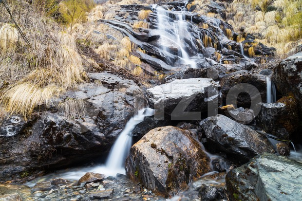 Serene waterfall from the melting snow on mountain during spring  in Annapurna mountains, Nepal Stock Photo