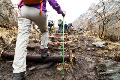 People hiking up hilly terrain to Annapurna Base Camp, Nepal Stock Photo