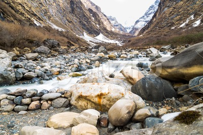 Picturesque of a valley with river and mountains with melting snow during spring on trekking route to Annapurna Base Camp, Nepal Stock Photo