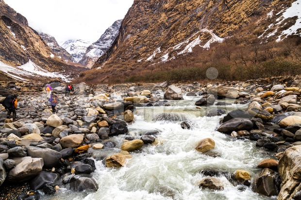 A group of people hiking on scenic snowy mountain and river en-route to Annapurna Base Camp, Nepal