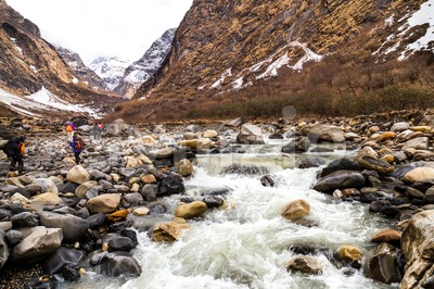 A group of people hiking on scenic snowy mountain and river en-route to Annapurna Base Camp, Nepal Stock Photo