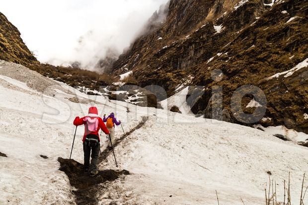 Two females hiking on a snowy trail towards the mountain in Nepal Annapurna circuit
