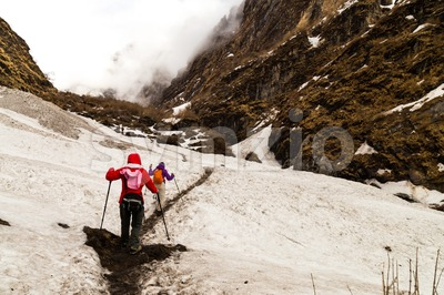 Two females hiking on a snowy trail towards the mountain in Nepal Annapurna circuit Stock Photo