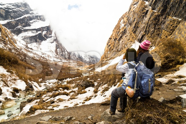 Two female hikers resting while enjoying the serene view of the snowy trek in Nepal Annapurna trekking route