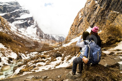 Two female hikers resting while enjoying the serene view of the snowy trek in Nepal Annapurna trekking route Stock Photo