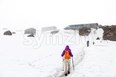 Female hiking on snow trail towards Annapurna base camp in Nepal Stock Photo