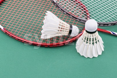 Two new badminton shuttlecock with rackets on green mat court Stock Photo