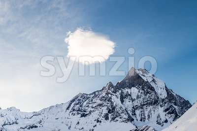 Peak of Mount Machapuchare or popularly known as Fish Tail with a piece of cloud over it as viewed from Annapurna Base Camp Stock Photo