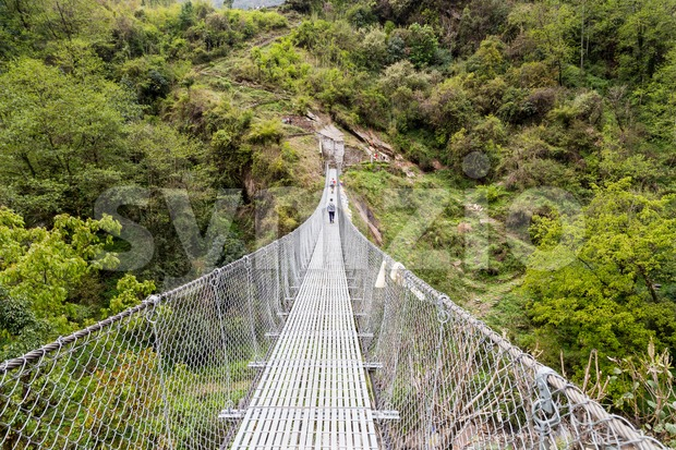 Hikers crossing a long metal suspension bridge in Nepal Stock Photo