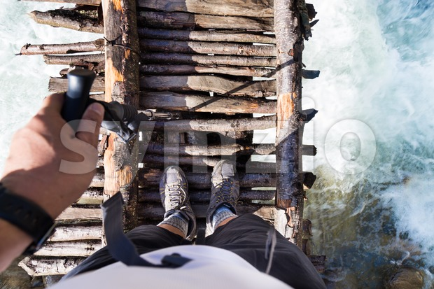 Perspective view of hiker crossing the many wooden bridges while hiking in Nepal's Annapurna circuit Stock Photo