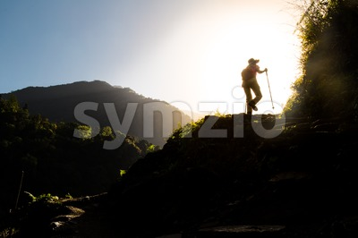 People in silhouette hiking towards sunrise Stock Photo