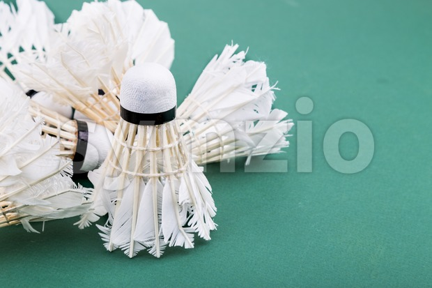 Heaps of used and worned out badminton shuttlecock on green court Stock Photo