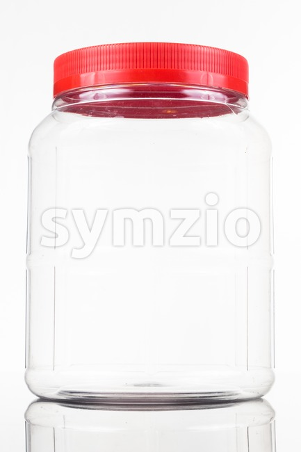 Large translucent plastic PVC jar with red cover isolated in white Stock Photo
