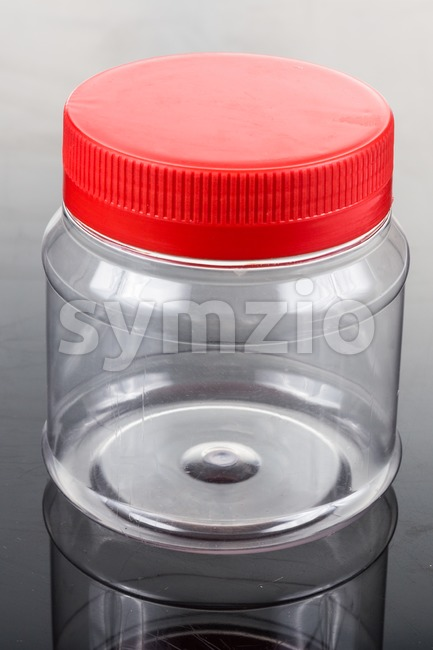 Translucent plastic PVC jar with red cover isolated in black Stock Photo
