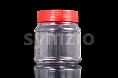 Small translucent plastic PVC jar with red cover isolated in black Stock Photo