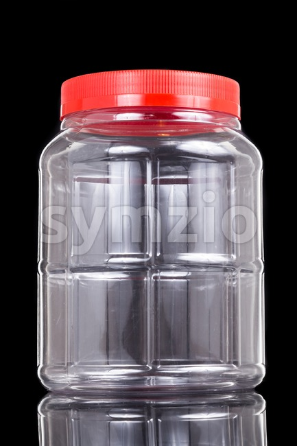 Large translucent plastic PVC jar with red cover isolated in black Stock Photo