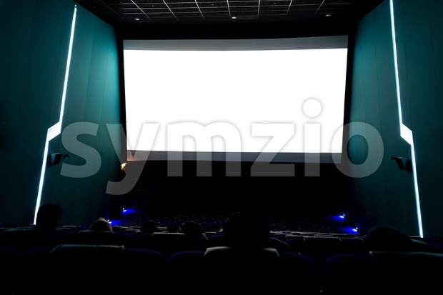 Viewers watching movie at cinema with screen isolated in white. Long exposure shot Stock Photo
