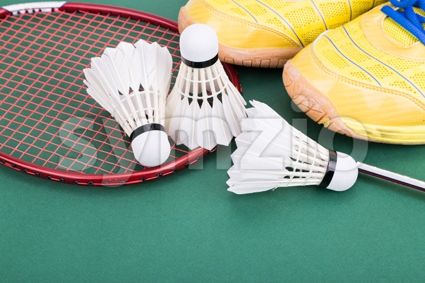 Three badminton shuttlecock with racket and shoes on green court Stock Photo