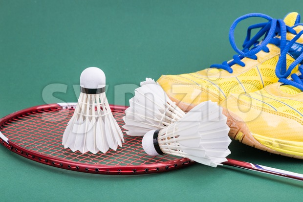 Three new badminton shuttlecock with racket and shoes on green mat PVC court