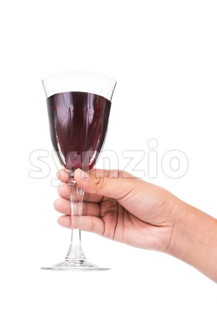 Hand holding red wine in crystal glass and ready to toast and cheers