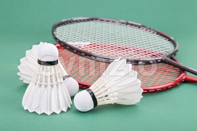 Three new badminton shuttlecock with rackets on green mat court Stock Photo