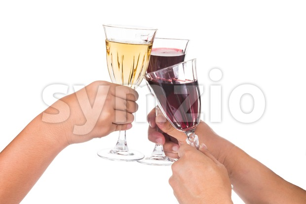 Three people knocking glasses and toasting red and white wine in crystal glass