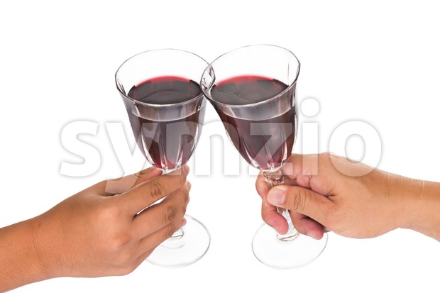Two hands knocking glasses and toasting red wine in crystal glasses Stock Photo