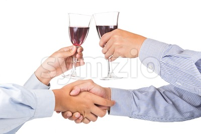 Men shaking hands and toasting red wine in crystal glass Stock Photo