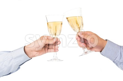 Hands in long sleeve shirt toastingwhite wine in crystal glasses Stock Photo