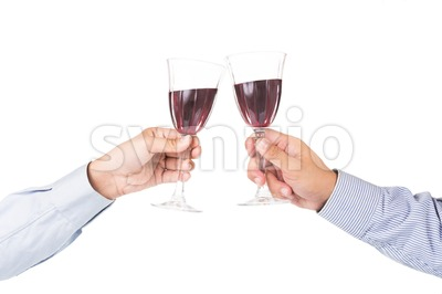 Hands in long sleeve shirt toasting red wine in crystal glasses Stock Photo