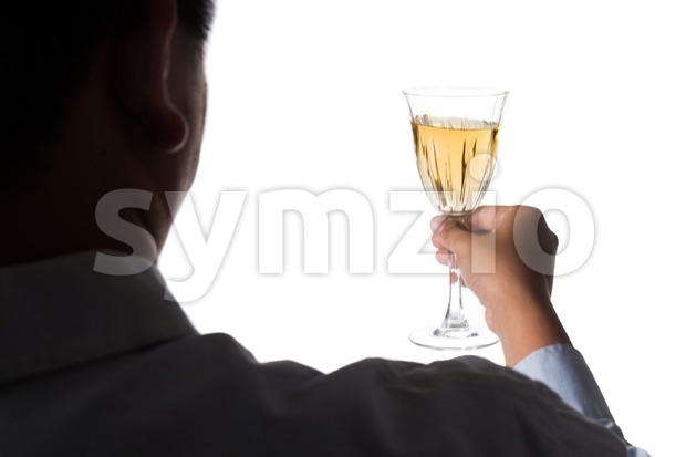 Silhouette image of man holding white wine in crystal glass and ready to toast and cheers