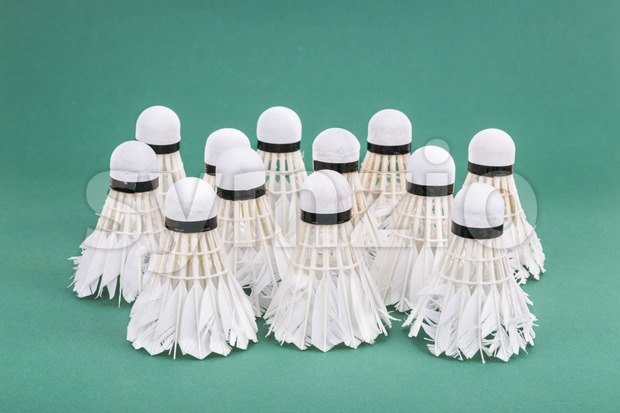 Group of used and worned out badminton shuttlecock on green mat PVC court