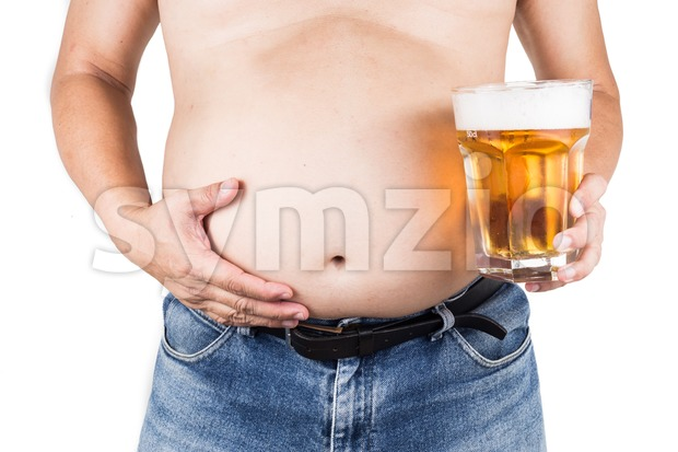 Obese man with big belly holding a glass of refreshing cold beer Stock Photo