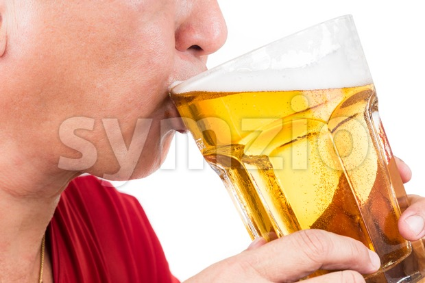 Matured man drinking a large mug of cold refreshing beer Stock Photo