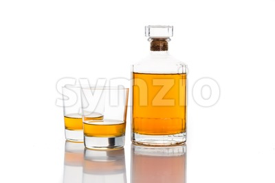 Whiskey bottle with glass of whiskey neat isolated in white Stock Photo