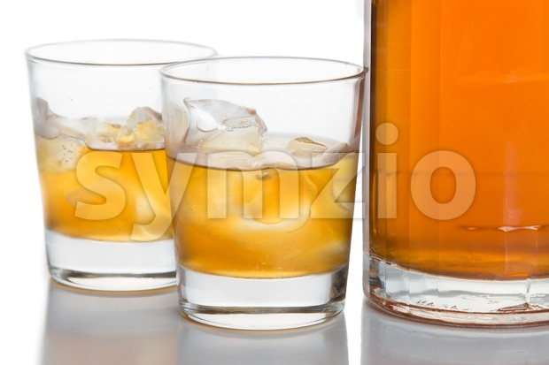 Glasses of whiskey on the rocks and a whiskey bottle isolated in white Stock Photo