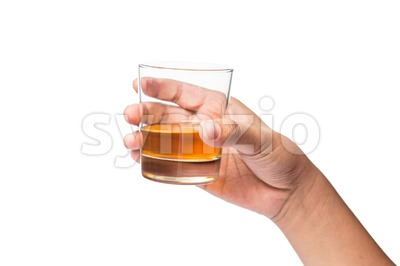 Hand holding a glass of whiskey on neat, ready to toast cheers Stock Photo