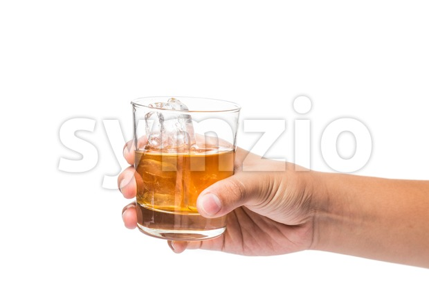 Hand holding a glass of cognac brandy on the rock ready to toast cheers Stock Photo